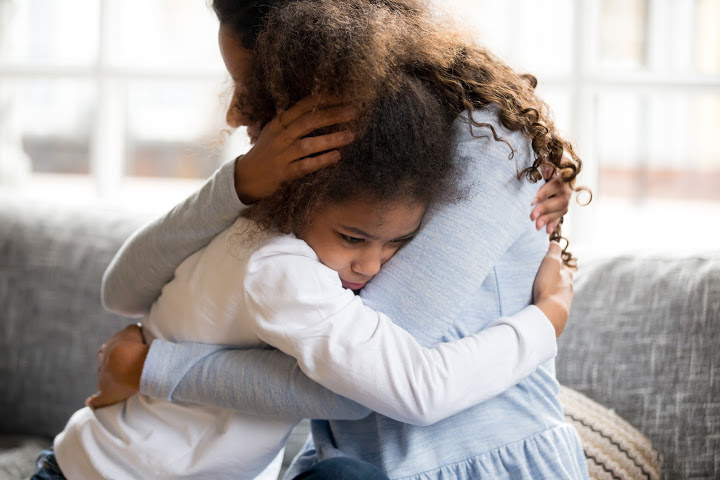 parent hugs sad child