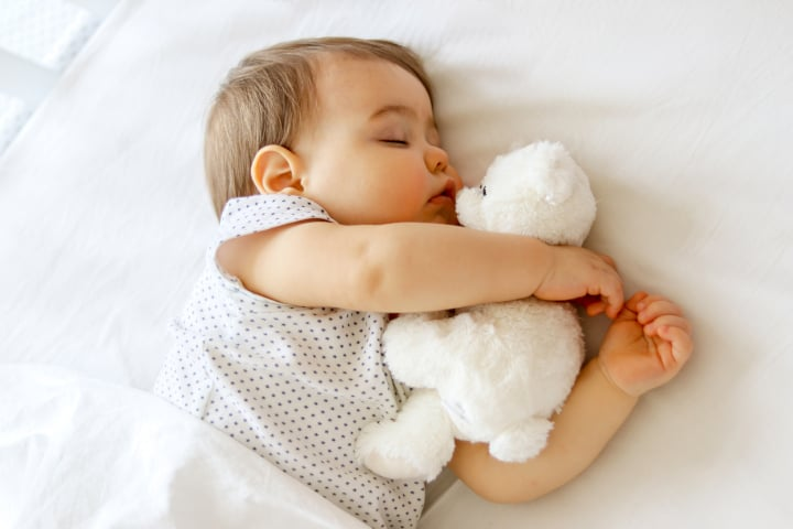 Baby sleeps with a stuffed toy with parents providing effective parenting