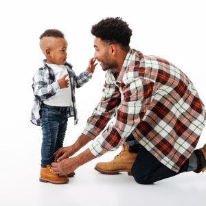 Father ties shoes for son and smiles - positive parenting