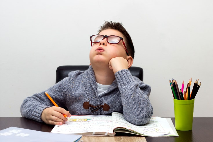 Boy looks up from homework feeling bored - Positive punishment examples