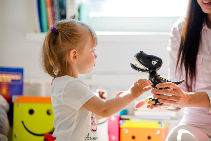 Mom gives girl a toy dinosaur - Positive reinforcement examples