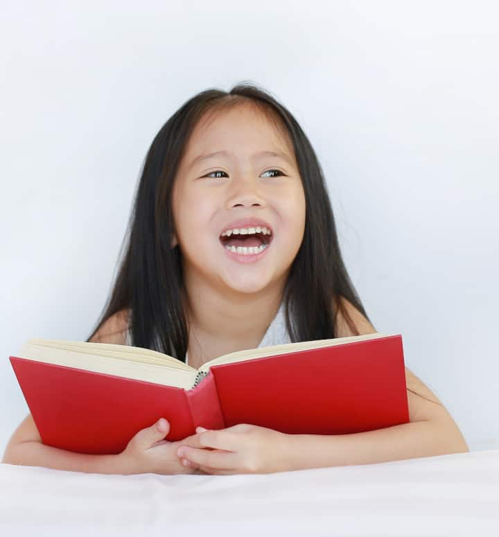 girl smiles with book open - positive reinforcement psychology