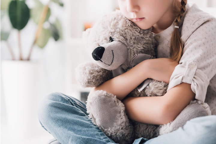 Girl hugs teddy bear - forms of discipline matter as too much harsh disciplining causes suffering