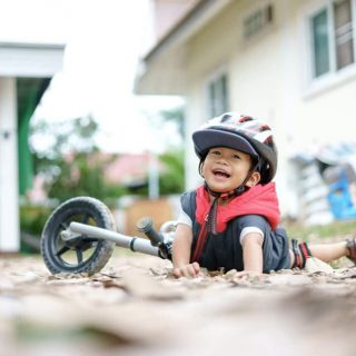 Boy falls off bike but smiles - resilience