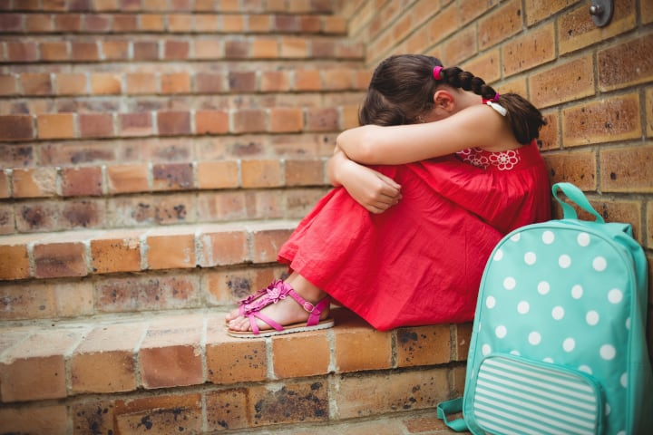 Girl sits on staircase made of brick and buries her head feeling sad, caused by insufficient resilence factors