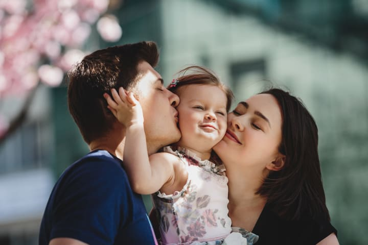 Young parents kiss little girl on the cheek from both sides under blooming pink tree, attachment with parents is a resilience protective factor