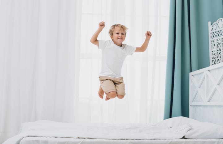 boy jumps on bed - resilience theory