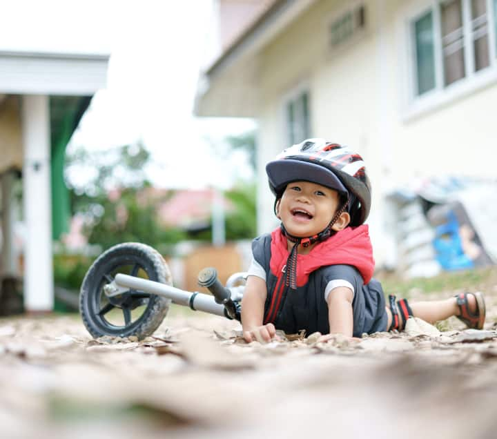 Boy falls off from bike and laughs, an example of resiliance