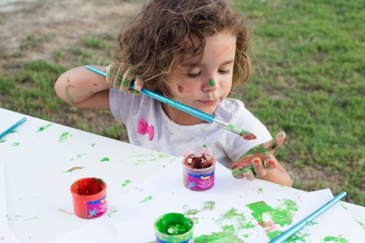 girl in messy shirt paints with several color - importance of sensory play and brain development