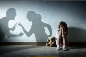 shadows of parents fighting and girl sits on ground crying