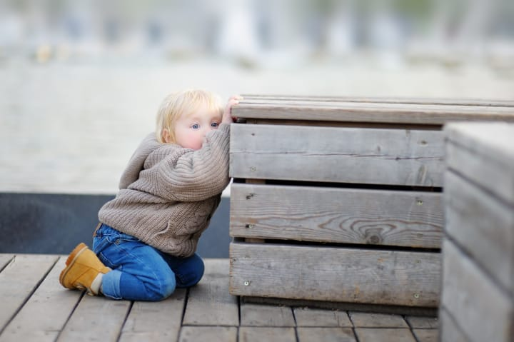 A child kneeling next to a bench - slow to warm up child