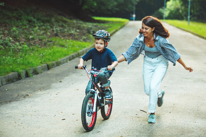 social psychologists mother pushes boy on bicycle