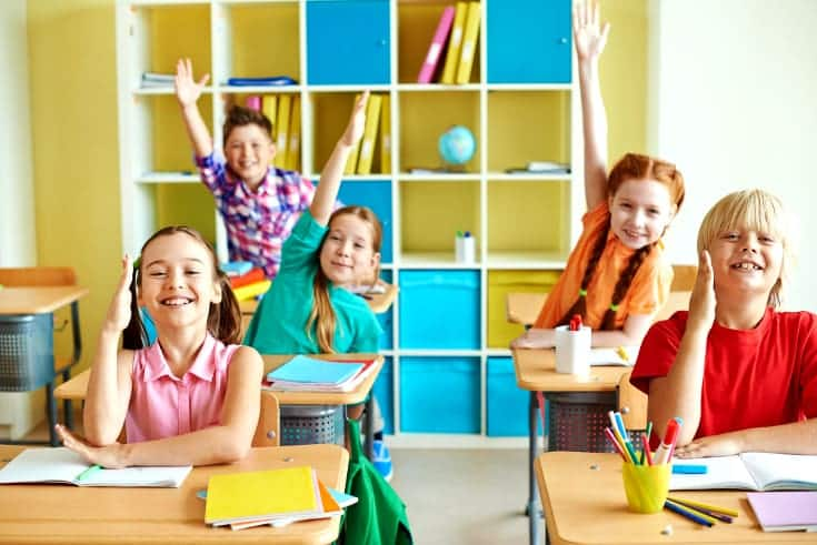 Boys and girls raise their hands enthusiastically in classroom - visual spatial learners