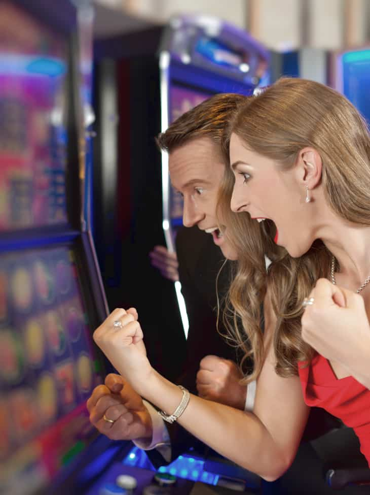 Couple win at slot machine in a casino. Addictive gambling is caused by spontaneous recovery psychology