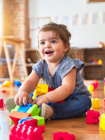 baby girl plays with toys in a room in a strange situation test