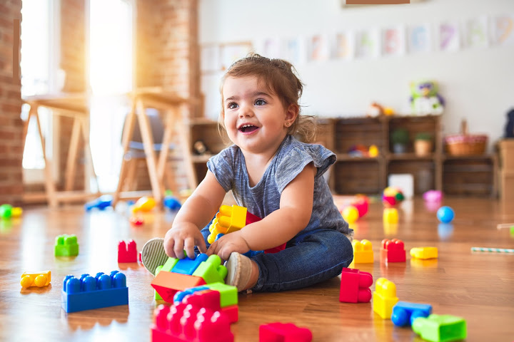 baby girl plays with toys in a room in the strange situation experiment in which psychologists study the science of attachment