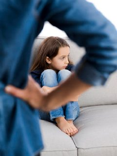 girl sits on couch in front of a strict parent