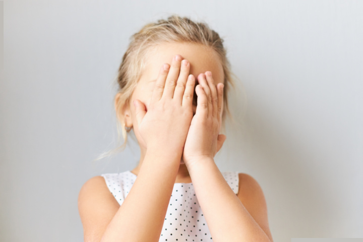 girl covers face with hands with strong reactions we help kids cope with stress