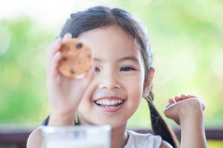 girl shows cookie with a smile is an example of teaching children respect and being respectful