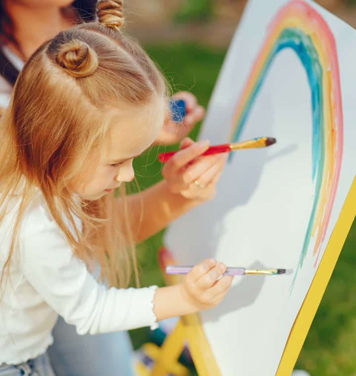 Girl paints rainbow with Mom on standup board - the importance of play in child development