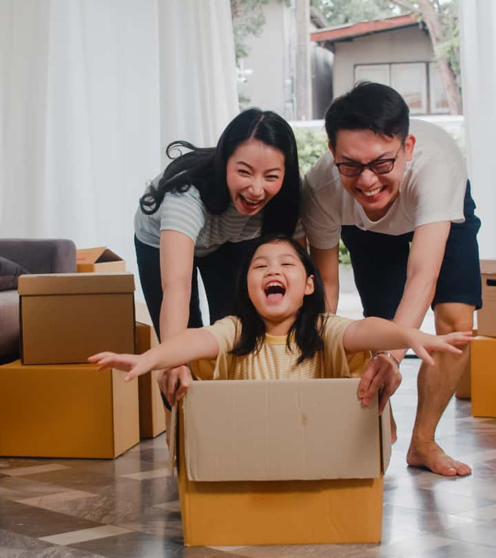 Mom and Dad push girl sitting in cardboard box to play - the importance of play in the early years