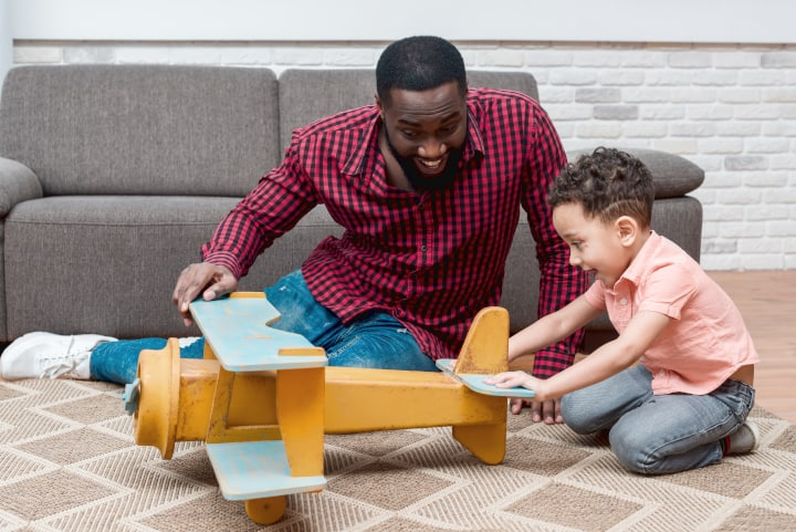 Man plays toy plane with son and are both smiling, no need to time out kids
