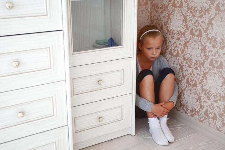 Sad little girl sitting in the corner of a room next to a dresser in a time out