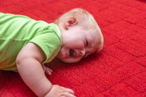 Toddler kneeling on ground having a temper tantrum