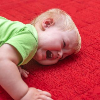 Toddler kneeling on ground having a temper tantrum
