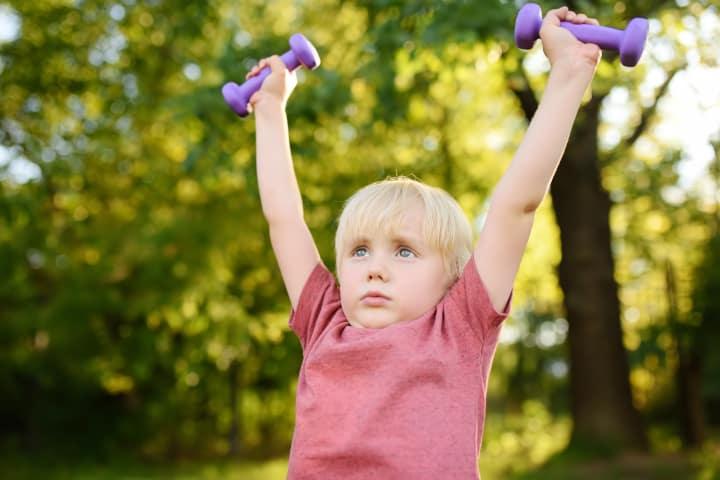 Boy lifts dumbbell weights - toughen up