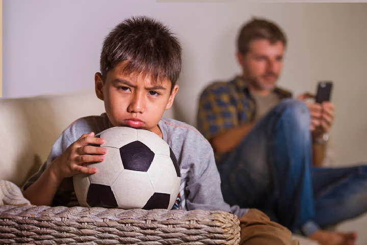 uninvolved parent ignores boy with soccer