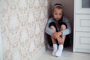 girl cries in a corner due to bad parenting