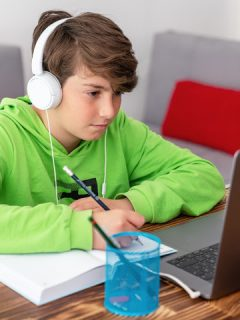 boy with headphones looks at laptop and writes why distance learning doesn't work