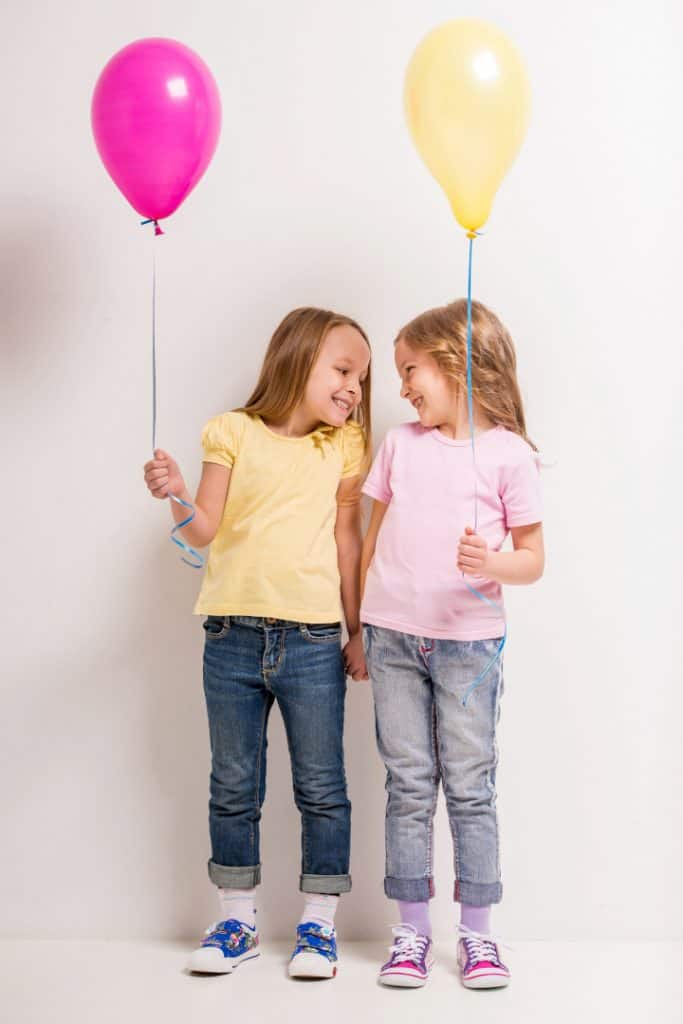 Two girls chat with smile while holding a pink and a yellow helium balloons - why is play important in early childhood