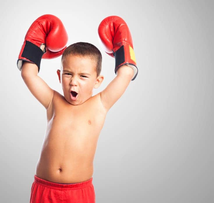 Boy in boxing gloves raises arms and roars - Positive words for kids, encouraging words for kids and positive notes can all boost confidence well-encouraged